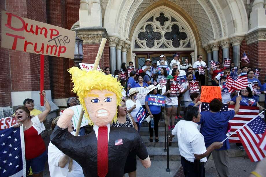 3000 x 2000~~$~~An anti-Trump supporter holds a Donald Trump pinata as Hispanic activists and community leaders speak at an anti-Trump rally outside the Cathedral Shrine of Guadalupe in Dallas on Monday, Sept. 14, 2015. (Ben Torres/Dallas Morning News/TNS) Photo: McClatchy-Tribune News Service