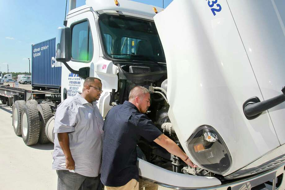 Stafford Wilson, left, a driver advocate, and Julian Leal, a driver, both for Jetco Delivery, consult during a pre-trip inspection.  Photo: Gary Fountain, Freelance / Copyright 2015 by Gary Fountain