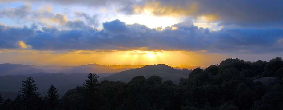 A setting sun casts beams of light through a broken layer of cumulus, viewed from 2,572-foot Borel Hill at Russian Ridge Open Space Preserve, looking out toward the west over coastal foothills to the ocean Photo: Deane Little, Special To The Chronicle