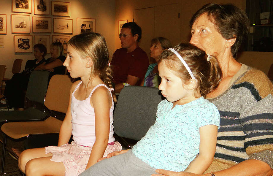 "Westporters Anna Maria Micu and granddaughters Adrianna, 4, and Alessandra, 7, enjoy a Grandparents Day screening of the musical comedy film ""Annie"" at the Westport Library. Photo: Mike Lauterborn / For Hearst Connecticut Media / Westport News"