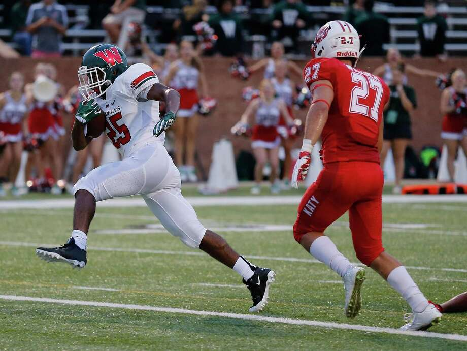 The Woodlands' Jordan Talford (25) scores in the first quarter as he crosses the goal line in front of Katy's Collin Wilder (27) providing the Highlanders' only points in a 14-7 loss. Photo: Bob Levey, Photographer / ©2015 Bob Levey