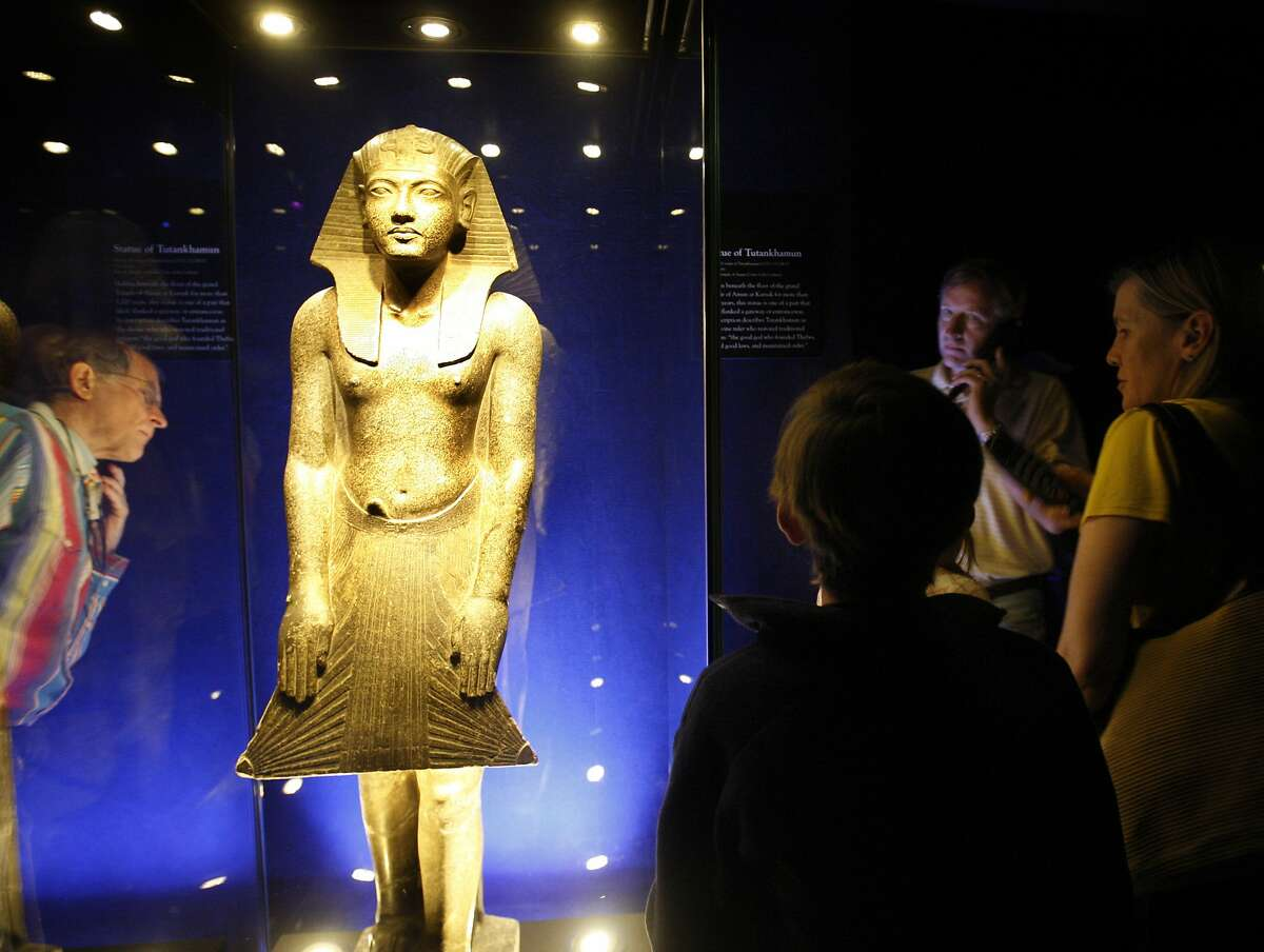 Visitors in the first group allowed in study a statue of Tutankhamun in the King Tut exhibit after it opened to the public at the de Young Museum in San Francisco, Calif., on Saturday, June 27, 2009.