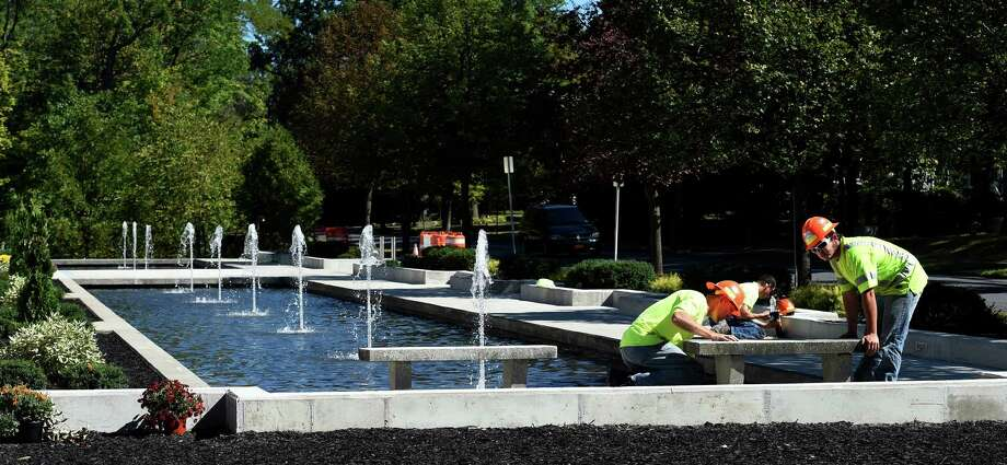 Andrew Bentley, right, Robert Bultman, foreman,left from the Bellamy Construction Company of Ballston Spa put the finishing touches on the fountain system at the First Unitarian Society Tuesday morning Sept. 15, 2015 in Schenectady, N.Y.  Worker David Nicola applies caulking to the joints in the background..  (Skip Dickstein/Times Union) Photo: SKIP DICKSTEIN / 00033369A