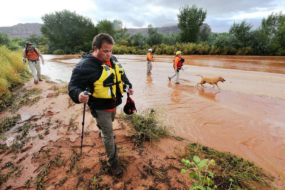 Members of Arizona's Mojave County search and rescue team use dogs to search for bodies after a wall of water swept away vehicles in the Utah-Arizona border area. Photo: Scott G Winterton, Associated Press