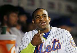New York Mets Yoenis Cespedes smiles in the dugout after hiting a third-inning, solo, home run in a baseball game against the Miami Marlins in New York, Monday, Sept. 14, 2015. (AP Photo/Kathy Willens)