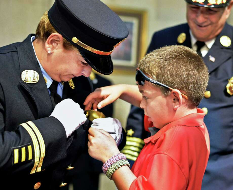 Kimberly Ciprioni, left, has her new Captain's shield pinned on by her son Anthony, 10, as three Albany City firefighters are promoted during a ceremony at City Hall Tuesday, Sept. 15, 2015 in Albany, NY. The ceremony also saw David Newton promoted to battalion chief and Joshua Kapczynski to lieutenant. (John Carl D'Annibale / Times Union) Photo: John Carl D'Annibale / 00033350A