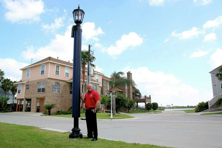 Nassau Bay City Manager Chris Reed stands by one of the new solar-powered street lamps that are replacing older models in the city. The project is one of the steps that won the city recognition from Scenic Texas. Nassau Bay City Manager Chris Reed stands by one of the new solar-powered street lamps that are replacing older models in the city. The project is one of the steps that won the city recognition from Scenic Texas. Photo: Pin Lim, Freelance / Copyright Forest Photography, 2015.