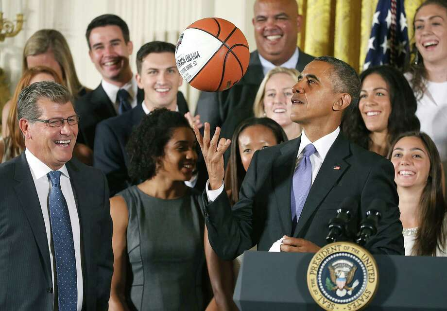 U.S. President Barack Obama tosses up a basketball given to him by coach Geno Auriemma, left, while honoring the 2015 NCAA Women's Basketball Champion University of Connecticut Huskies during a ceremony in the East Room at White House September 15, 2015 in Washington, DC. President Obama honored the Huskies for winning their third consecutive title with 10 overall. (Photo by Mark Wilson/Getty Images) Photo: Mark Wilson / Getty Images / 2015 Getty Images