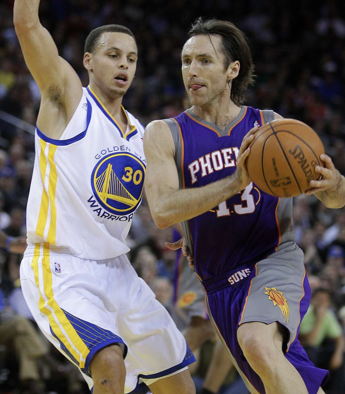 Phoenix Suns' Steve Nash, right, drives to the basket as Golden State Warriors' Stephen Curry defends on Feb. 7, 2011, in Oakland.