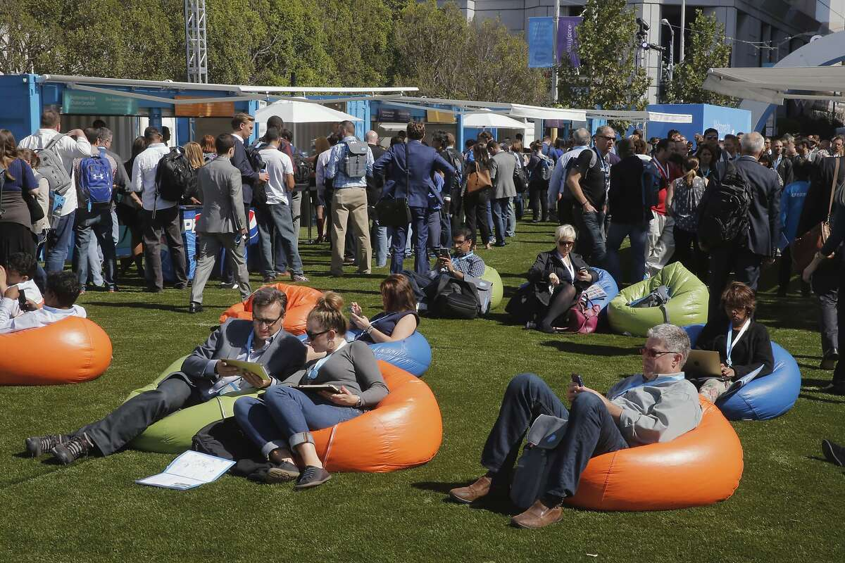 Attendees take a break on the bean bag chairs along Howard St. as Dreamforce gets underway at the Moscone Center in downtown San Francisco, Calif., on Tues. September 15, 2015.