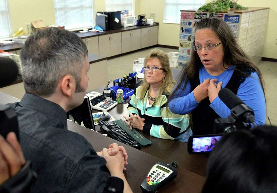 Rowan County Clerk Kim Davis, right, talks with David Moore following her office's refusal to issue marriage licenses at the Rowan County Courthouse in Morehead, Ky., Tuesday, Sept. 1, 2015. Although her appeal to the U.S. Supreme Court was denied, Davis still refuses to issue marriage licenses. (AP Photo/Timothy D. Easley) ORG XMIT: KYTE102 Photo: Timothy D. Easley / FR43398 AP