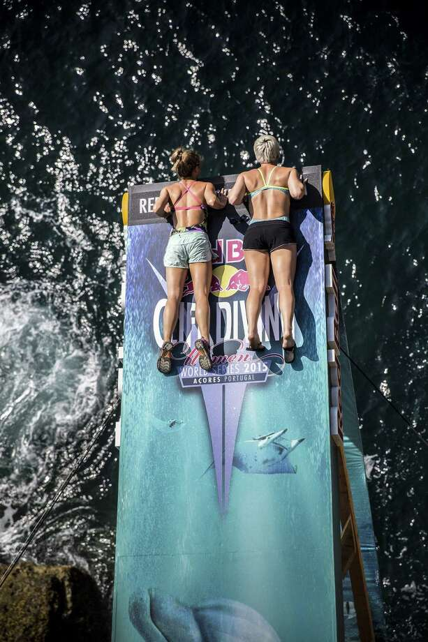 In this handout image provided by Red Bull, Tara Hyer-Tira (L) and Rachelle Simpson of the USA look at the view from the women's 20 metre platform during an open training day prior to the fifth stop of the Red Bull Cliff Diving World Series on July 15, 2015 at Islet Franca do Campo, Azores, Portugal. Photo: Handout, Getty Images / 2015 Red Bull