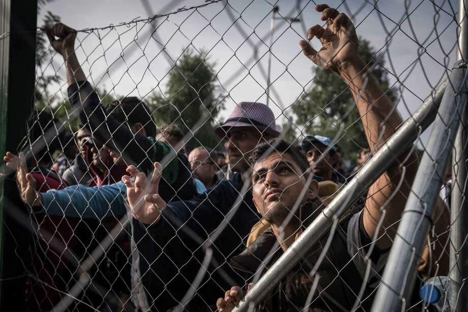 Migrants at the closed gate of a border crossing checkpoint to Hungary, which they hope to enter, in Horgos, Serbia, Sept. 15, 2015. Hungary declared a state of crisis along its border with Serbia early Tuesday, detaining 60 migrants and threatening to prosecute and imprison others trying to enter the country illegally from Serbia. (Sergey Ponomarev/The New York Times) Photo: SERGEY PONOMAREV, STR / New York Times / NYTNS