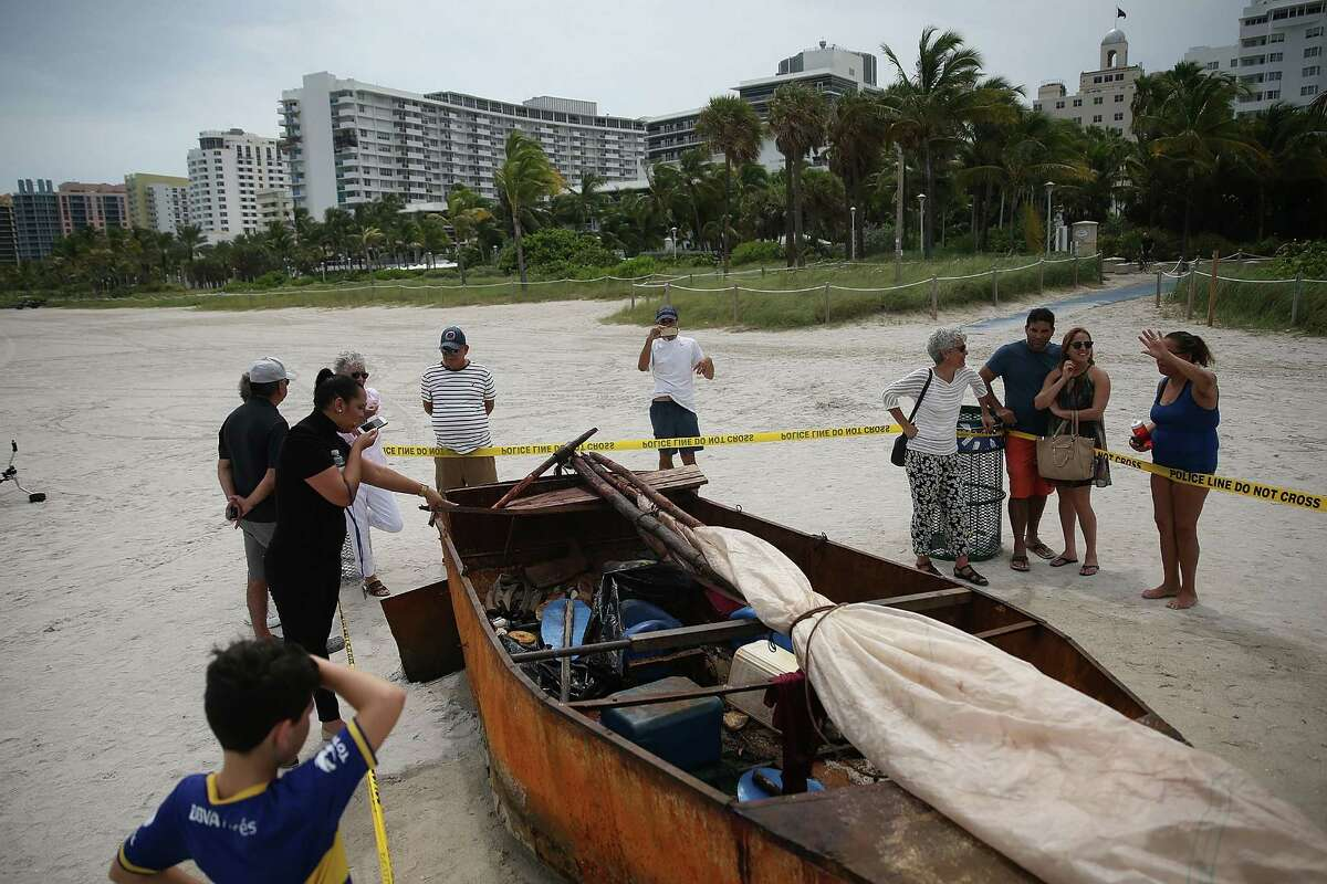 People look at a Cuban migrant boat that brought 12 people and a dog to the beach on Sept. 15, 2015 in Miami Beach, Florida. Immigrants are increasingly choosing the Southwest border crossing instead of the treacherous waters to Miami, for decades the traditional route.