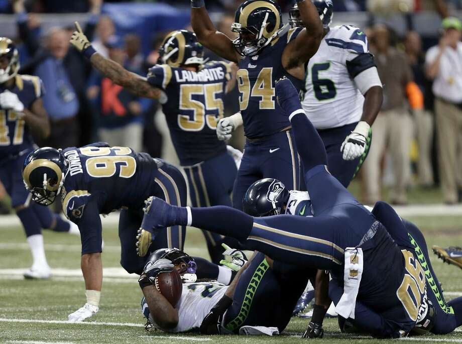 Seattle Seahawks running back Marshawn Lynch, bottom, lands on his back after being stopped on fourth down as St. Louis Rams players celebrate on the final play in overtime of an NFL football game Sunday, Sept. 13, 2015, in St. Louis. The Rams won 34-31. (AP Photo/Tom Gannam) Photo: Tom Gannam, Associated Press