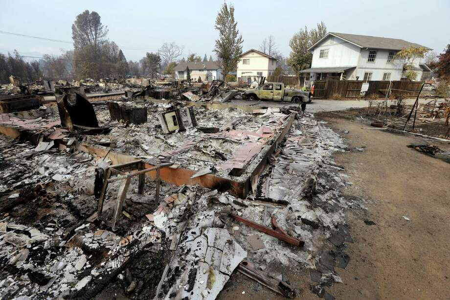 Houses remain standing and with little damage in view of others that were destroyed in a wildfire several days earlier, Tuesday, Sept. 15, 2015, in Middletown, Calif. The fire that sped through Middletown and other parts of rural Lake County, less than 100 miles north of San Francisco, has continued to burn since Saturday despite a massive firefighting effort. (AP Photo/Elaine Thompson) Photo: Elaine Thompson, STF / Associated Press / AP