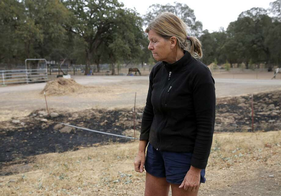 Cheryl Johnston, a Hidden Valley Lake resident, pauses while reflecting on the devastation caused by the Valley Fire in Hidden Valley Lake, California, on Tuesday, Sept. 15, 2015. Johnston saved several horses, fought spot fires and eventually stayed overnight in a barn Saturday night as the Valley Fire spread. Photo: Connor Radnovich, The Chronicle