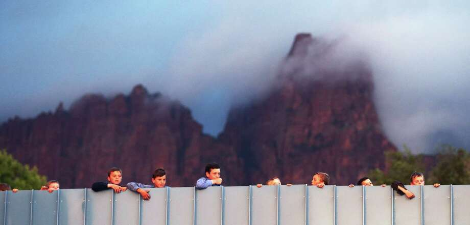 Residents of Hildale, Utah and Colorado City, Ariz.,  watch as work goes on to clean debris off of a bridge area after a flash flood on Tuesday, Sept. 15, 2015 in Colorado City, Ariz.  A wall of water swept away vehicles in the Utah-Arizona border town Monday, killing several people.  (Scott G Winterton/The Deseret News via AP)  SALT LAKE TRIBUNE OUT; MAGS OUT; MANDATORY CREDIT Photo: Scott G Winterton, MBO / Associated Press / The Deseret News