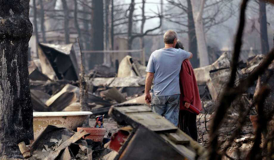 Richard and Kathie Reeves survey the remains of the home belonging to some friends that was destroyed in a wildfire. Officials said Tuesday that nearly 600 homes had been destroyed by the fires.