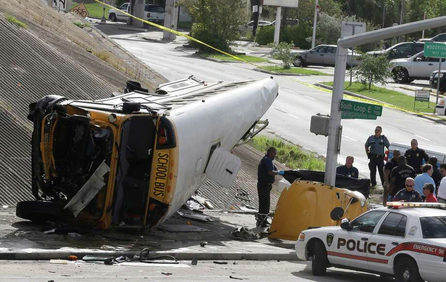 Investigators work around a Houston school bus, left, after it drove off a highway overpass, Tuesday, Sept. 15, 2015, in Houston, killing two students and seriously injuring three other people, police and school officials said. (AP Photo/Pat Sullivan) ORG XMIT: TXPS103 Photo: Pat Sullivan / AP