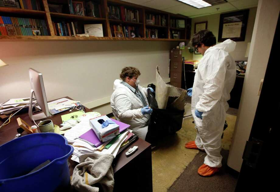 An environmental cleanup crew works in the office of Delta State University history professor Ethan Schmidt in Cleveland, Miss., on Tuesday, Sept. 15, 2015. Police say Shannon Lamb, an instructor at the same school, killed Schmidt in his office Monday morning. Lamb later died in Greenville of an apparent self-inflicted gunshot wound. (AP Photo/Rogelio V. Solis) ORG XMIT: MSRS102 Photo: Rogelio V. Solis / AP