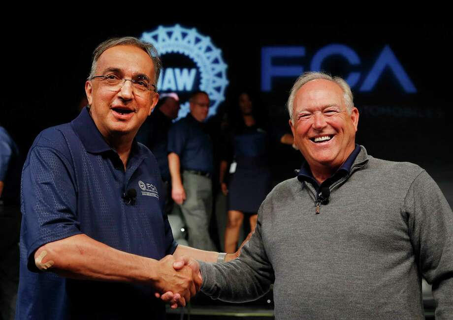 FILE - In this July 14, 2015, file photo, Fiat Chrysler Automobiles CEO Sergio Marchionne, left, and United Auto Workers President Dennis Williams shake hands during a ceremony to mark the opening of contract negotiations in Detroit. The United Auto Workers union and Fiat Chrysler have reached a tentative deal on a new contract for about 40,000 workers that will serve as a pattern for pacts with General Motors and Ford. Terms of the deal were not disclosed Tuesday, Sept. 15, but both sides said a news conference would be held later in the evening with Williams and Marchionne. (AP Photo/Paul Sancya, File) Photo: Paul Sancya, STF / AP