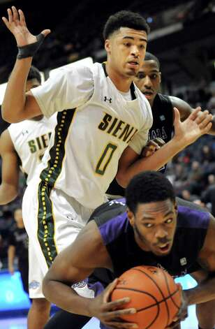 Siena's Javion Ogunyemi, center, loses the rebound to Niagara's James Suber during their first round game in the MAAC Championship on Thursday, March 5, 2015, at Times Union Center in Albany, N.Y. (Cindy Schultz / Times Union) Photo: Cindy Schultz / 10030857A