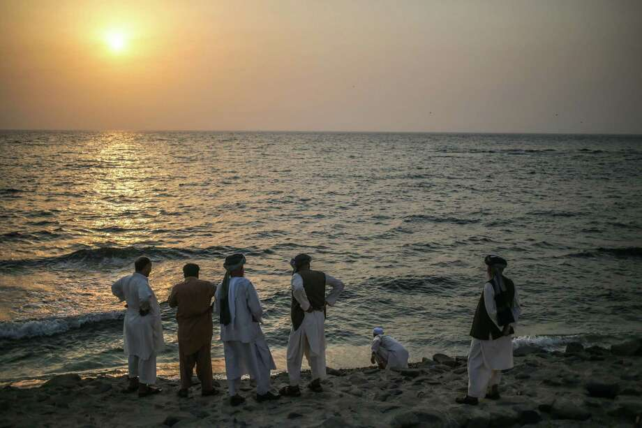 "Afghani pilgrims observe the sunset over the Red Sea at the Jeddah corniche, a few days before the annual ""Hajj"" pilgrimage begins, in Saudi Arabia, Monday, Sept. 14, 2015. (AP Photo/Mosa'ab Elshamy) Photo: Mosa'ab Elshamy, STF / AP"