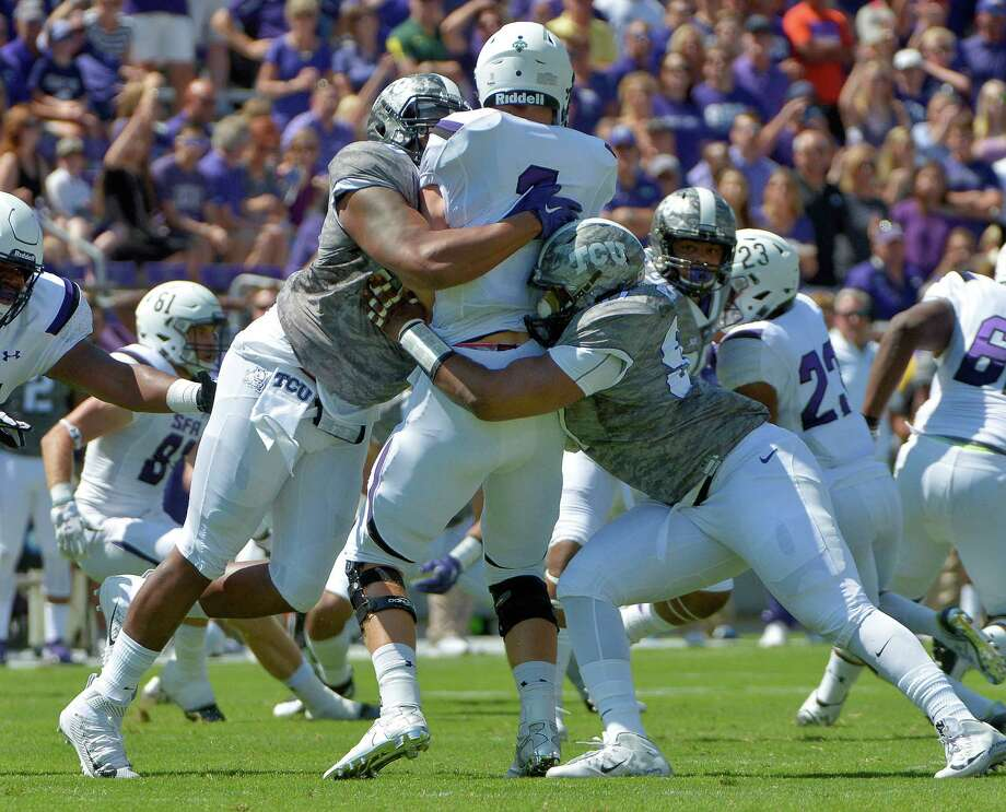 Stephen F. Austin quarterback Zach Conque gets a taste of the stoutness of TCU's defense in the form of Terrell Lathan, left, and Josh Carraway. Photo: Max Faulkner, MBR / Fort Worth Star-Telegram