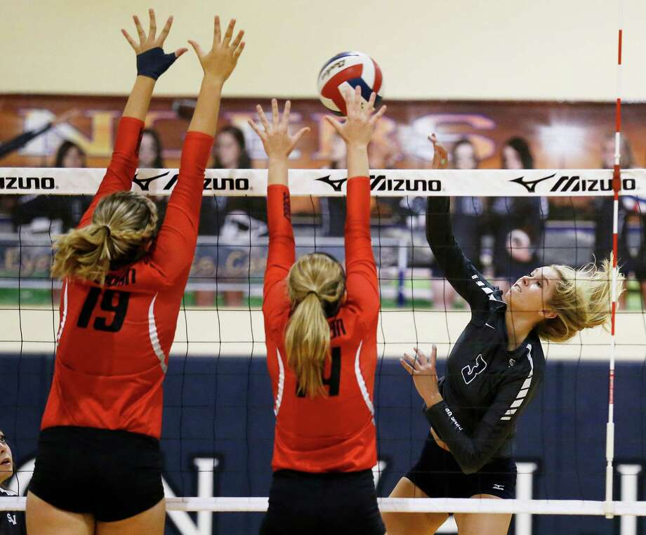 Smithson Valley's Maja Kaiser (03) attempts a hit against New Braunfels Canyon's Brooke Vestal (19) and Haley Bradfute (14) during their game at Smithson Valley High School on Tuesday, Sept. 15, 2015. Photo: Kin Man Hui /San Antonio Express-News / ©2015 San Antonio Express-News