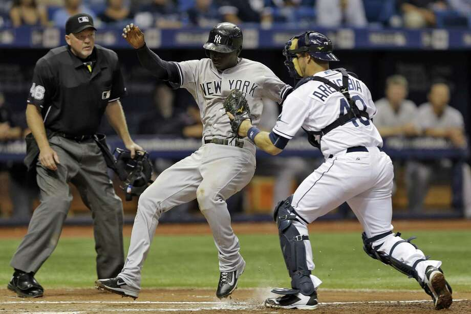 Tampa Bay Rays catcher J.P. Arencibia, right, tags out New York Yankees' Didi Gregorius, center, at home plate on a ball hit by Brett Gardner during the fifth inning of a baseball game Tuesday, Sept. 15, 2015, in St. Petersburg, Fla. At left is home plate umpire Ron Kulpa. (AP Photo/Chris O'Meara)  ORG XMIT: SPD112 Photo: Chris O'Meara / AP