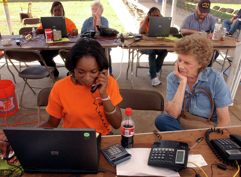 Verlon Jenkins-Tarr, right, waits as FEMA worker Ashante' Parker attempts to check the status of her FEMA application at a FEMA/Texas Disaster Recovery Center at Kountze High School after Hurricane Rita struck.  Photo: Beaumont Enterprise / THE BEAUMONT ENTERPRISE