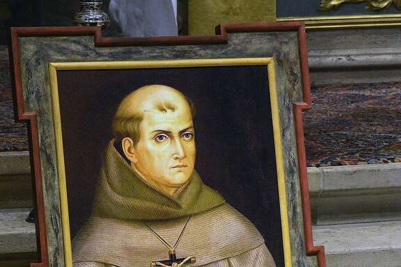 FILE -  In this May 6, 2015 file photo, a painting of Rev. Junipero Serra is seen above his grave inside the basilica at the Carmel Mission in Carmel, Calif. Pope Francis' apology for the Roman Catholic Church's crimes against indigenous peoples has not softened opposition among some California Native Americans to his decision to canonize 18th-century Franciscan missionary Junipero Serra, extolled by the Vatican as a great evangelizer, but denounced by some tribal officials as a destroyer of Native culture.(David Royal/The Monterey County Herald via AP, File) MANDATORY CREDIT