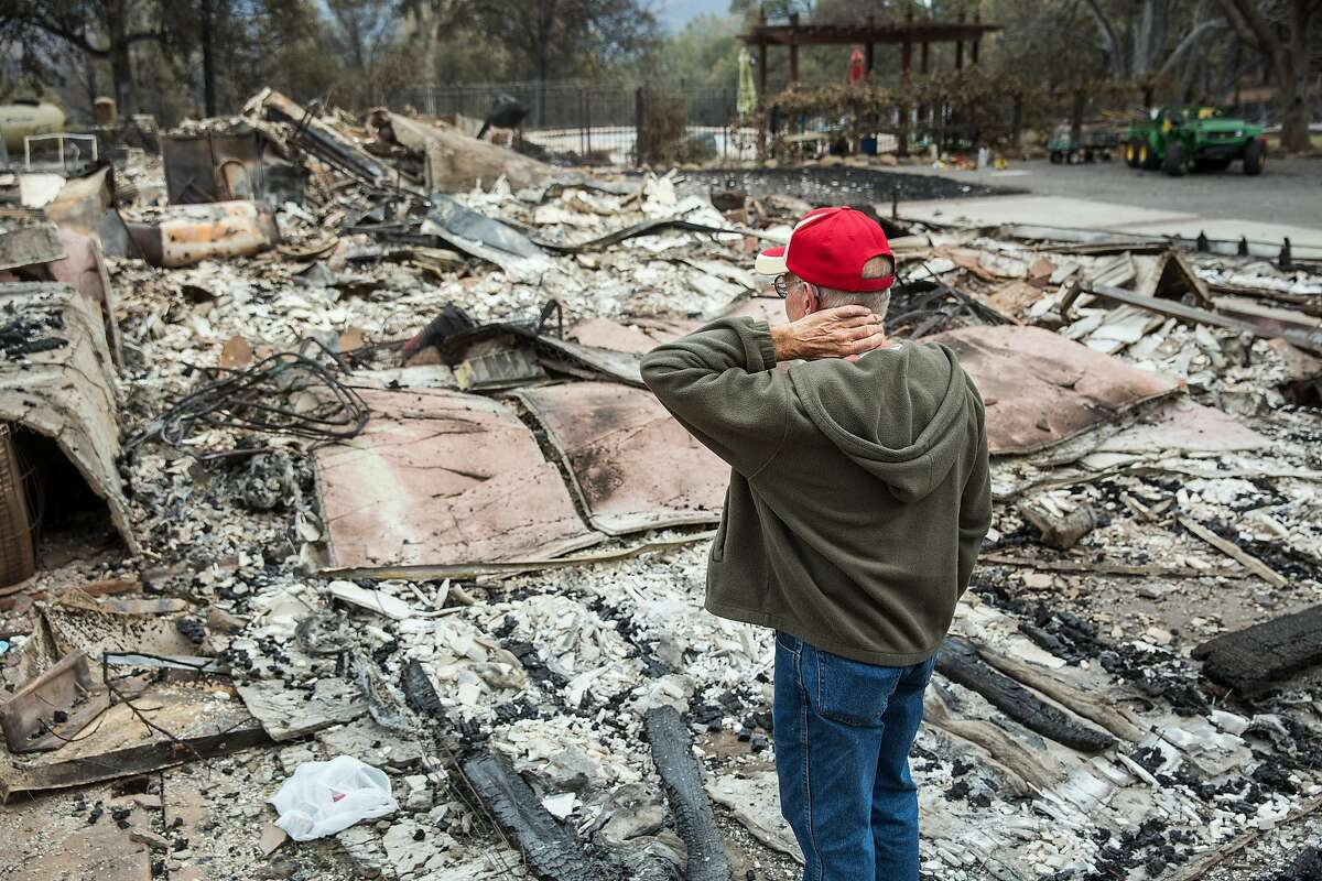 Jay Albertson takes a moment as he views his burned down home of 30 years after it was destroyed by the Valley Fire in Hidden Valley Lake, Calif., on Tuesday, Sept. 15, 2015.