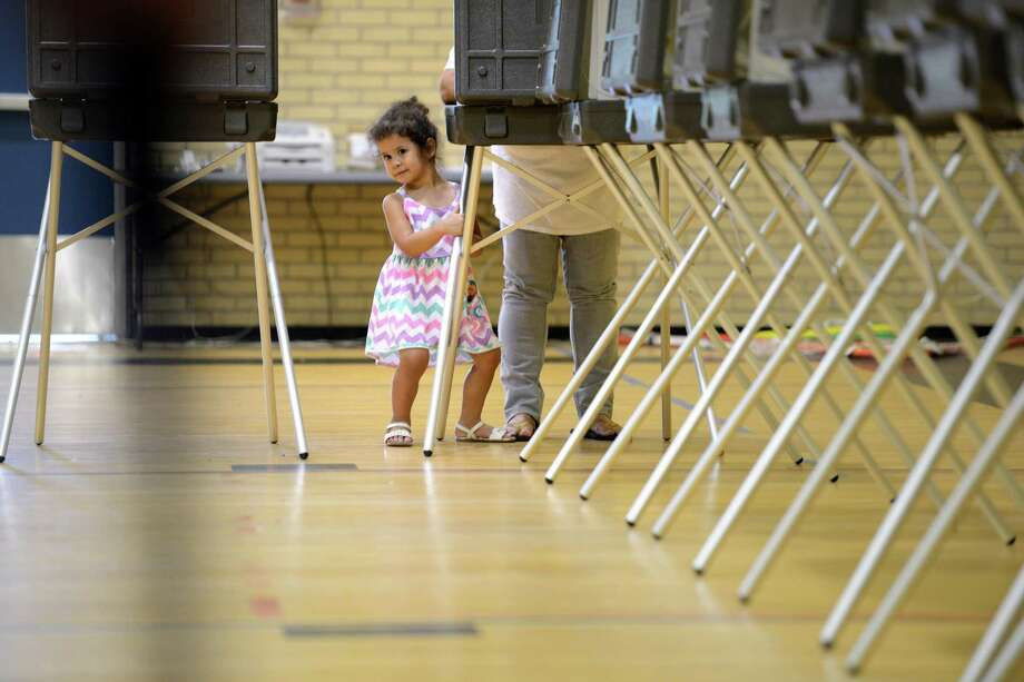 Two-year-old Karina Garcia helps her grandmother, Carmen Garcia, cast her vote at Blackham School in Bridgeport, Conn., Wednesday, Sept. 16, 2015, during the primary election. Photo: Autumn Driscoll, Hearst Connecticut Media / Connecticut Post