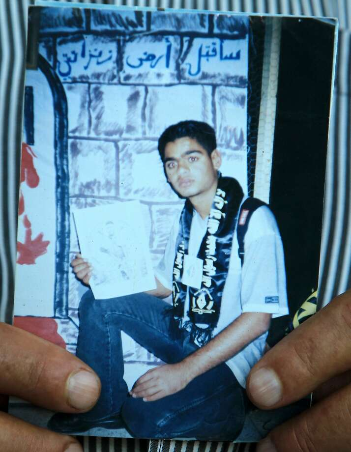 An undated portrait of Mohammed Allan is held by his father at the family home in the West Bank city of Nablus. Israel reinstated the detention without trial on September 16, 2015 of Palestinian detainee Mohammed Allan, who was held by Israel without trial and his recent two-month hunger strike brought him near death and increased tensions in the occupied West Bank. Photo: Jaafar Ashtiyeh, AFP / Getty Images