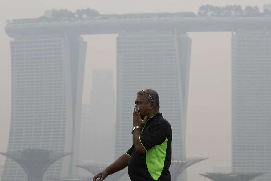 A man covers his nose during a hazy day in Singapore. A new study notes that farming plays a large role in smog and soot deaths in industrial nations. Photo: Ng Han Guan, Associated Press