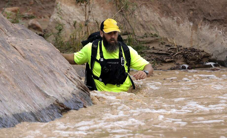 A member of a rescue team wades into the Virgin River during a search in Zion National Park for hikers who became trapped in a narrow desert canyon when a flash flood filled the chasm with water. Photo: Rick Bowmer, Associated Press