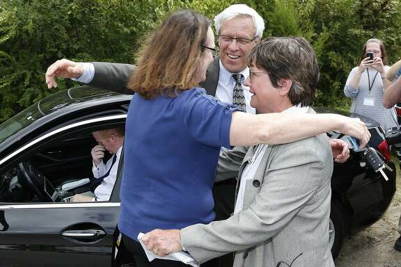 From left, Kathleen Lord, Don Knight, two of  Richard Glossips's attorneys, and Sister Helen Prejean, a death penalty opponent, embrace outside the Oklahoma State Penitentiary in McAlester Okla., Wednesday, Sept. 16, 2015, after the scheduled execution for Glossip was stayed.  Glossip was twice convicted of ordering the killing of Barry Van Treese, who owned the Oklahoma City motel where he worked. His co-worker, Justin Sneed, was convicted of fatally beating Van Treese and was a key prosecution witness in Glossip's trials.