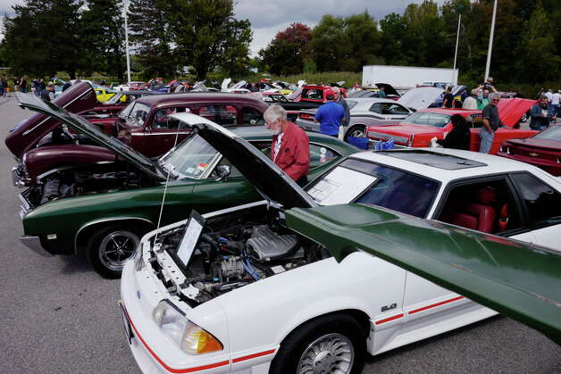 Visitors look over the cars on display during  the 3rd Annual Time Union Car Show at the Times Union Newspaper, on Sunday, Sept. 22, 2013 in Colonie, NY.  The event raises money for the Times Union Hope Fund.   (Paul Buckowski / Times Union) Photo: Paul Buckowski / 00023756A