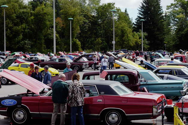 Visitors look over the cars on display during  the 3rd Annual Time Union Car Show at the Times Union on Sunday, Sept. 22, 2013 in Colonie, NY.  The event raises money for the Times Union Hope Fund.   (Paul Buckowski / Times Union) Photo: Paul Buckowski / 00023756A