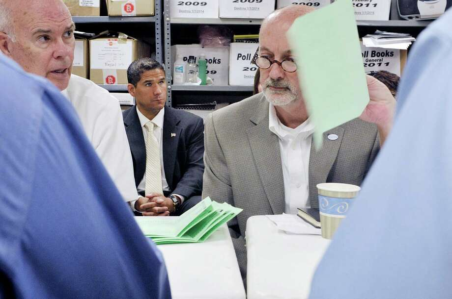 Tom Spargo, left, an election advisor to candidate Rodney Wiltshire, center, and  candidate Patrick Madden, right, look on at the Rensselaer County Board of Elections as absentee ballots in the Democratic primary for mayor were counted on Wednesday, Sept. 16, 2015,  in Troy, N.Y.   (Paul Buckowski / Times Union) Photo: PAUL BUCKOWSKI / 00033346A