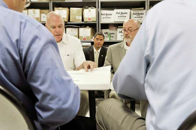 Tom Spargo, left, an election advisor to candidate Rodney Wiltshire, center, makes an objection to an absentee ballot as candidate Patrick Madden, right, looks on at the Rensselaer County Board of Elections on Wednesday, Sept. 16, 2015,  in Troy, N.Y.  The board of elections opened and counted the absentee ballots in the Democratic primary for mayor.  (Paul Buckowski / Times Union) Photo: PAUL BUCKOWSKI / 00033346A