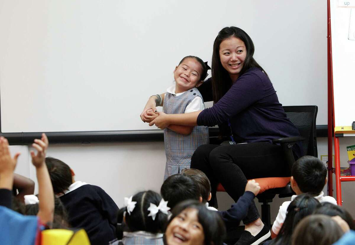 In Vanessa Chang's Kinder classroom, Yackyri Raga pretends to be a land scape worker during a guess the profession game Tuesday, Sept. 15, 2015, in Houston.