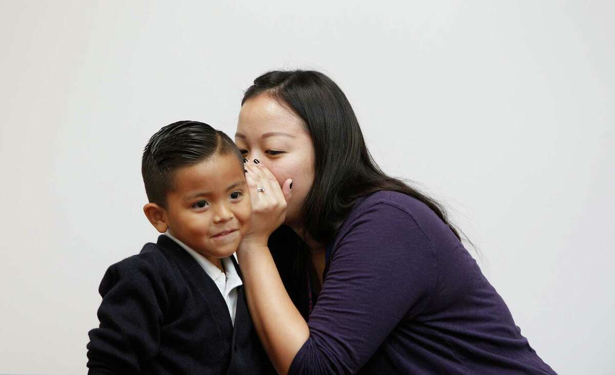 Kinder teacher Vanessa Chang's whispers to Adiel Munoz during a guess the profession game Tuesday, Sept. 15, 2015, in Houston.