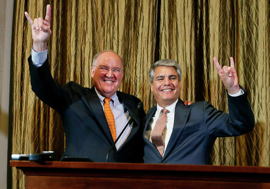 "Interim athletic director Michael Perrin and University of Texas president Gregory Fenves sign the ""Hook 'em Horns"" during a press conference, Wednesday, Sept. 16, 2015, announcing Steve Patterson's replacement after his departure the day before, at the University of Texas, in Austin, Texas. Photo: Ricardo Brazziell /Austin American-Statesman / Austin American-Statesman"