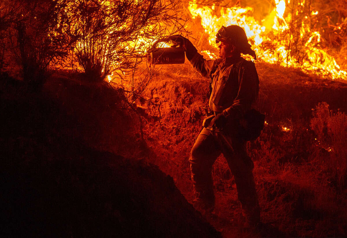 A firefighter lights a backfire while battling the Butte fire near San Andreas, California on September 12, 2015. According to state fire agency CAL FIRE, the fire has burned more than 65,000 acres and 86 homes.