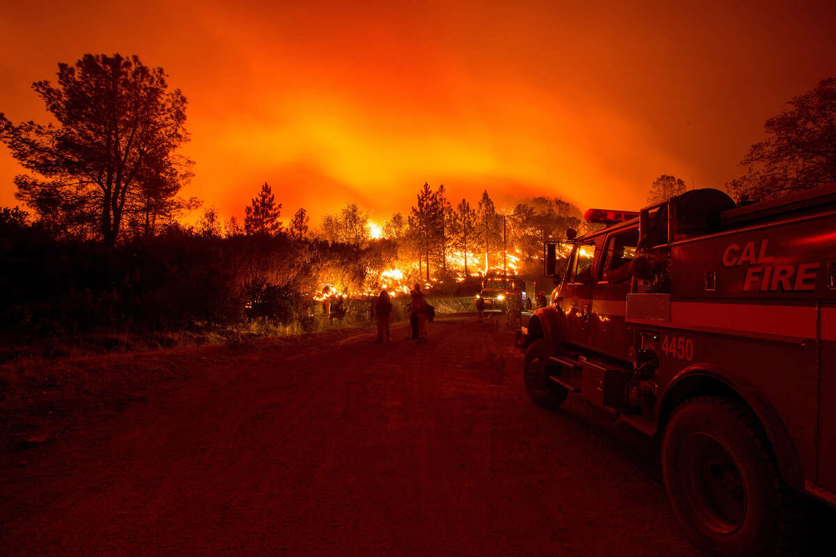 Firefighters monitor flames while battling the Butte fire near San Andreas, California on September 12, 2015. According to state fire agency CAL FIRE, the fire has burned more than 65,000 acres and 86 homes.