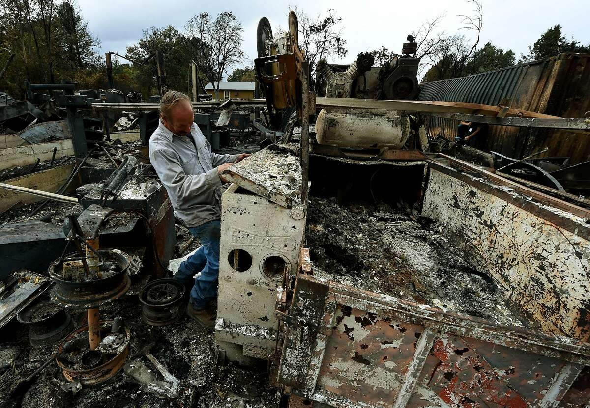 Business owner Larry Menzio looks at the remnants of his destroyed auto business after the Valley Fire swept through the town of Middletown, California, on September 16, 2015. The governor of California declared a state of emergency as raging wildfires spread in the northern part of the drought-ridden US state, forcing thousands to flee the flames. AFP PHOTO / MARK RALSTONMARK RALSTON/AFP/Getty Images