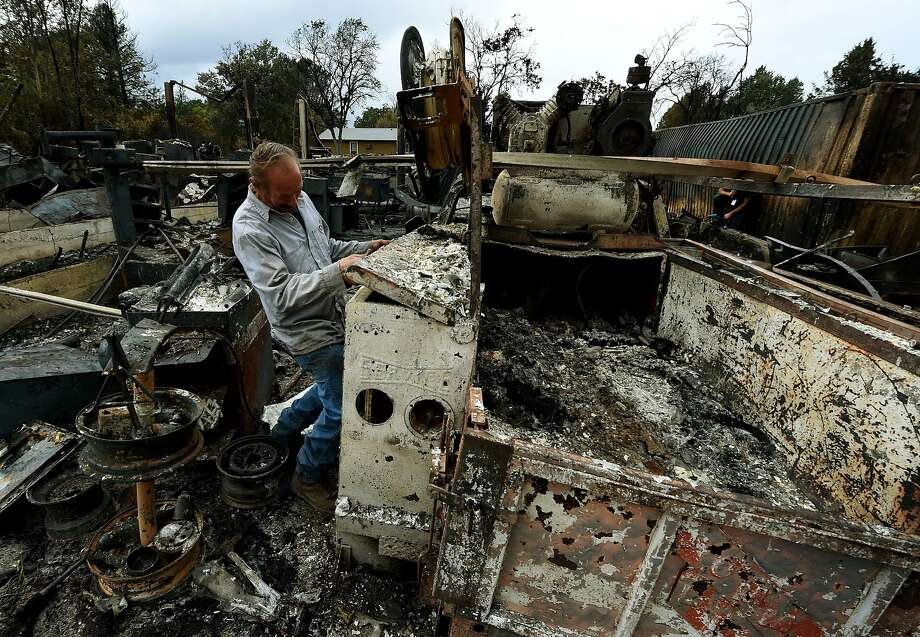 Business owner Larry Menzio looks at the remnants of his destroyed auto business after the Valley Fire swept through the town of Middletown, California, on September 16, 2015. The governor of California declared a state of emergency as raging wildfires spread in the northern part of the drought-ridden US state, forcing thousands to flee the flames.      AFP PHOTO / MARK RALSTONMARK RALSTON/AFP/Getty Images Photo: Mark Ralston, AFP / Getty Images